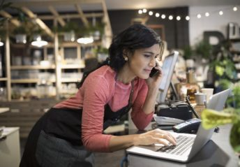Female shop owner working at laptop at plant shop counter