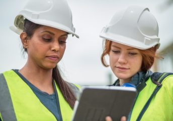 Two young women engineers on site checking details on digital tablet
