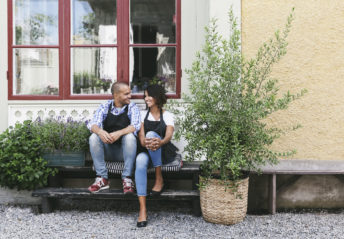 Smiling owners sitting on bench against window outside cafe
